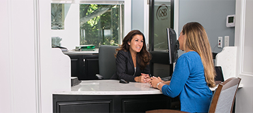 Two women talking at a desk