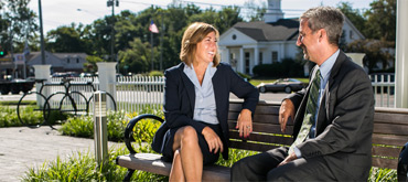 A man and a woman talking while sitting on a bench