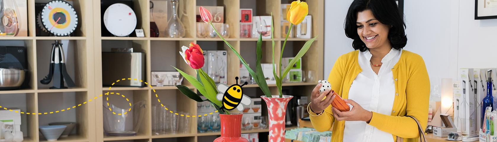 Woman looking at item with bee illustration on image.