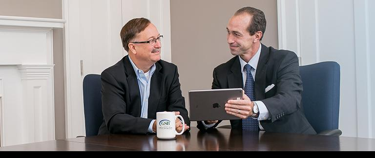 Bankers at a Discussion Table looking at an Ipad