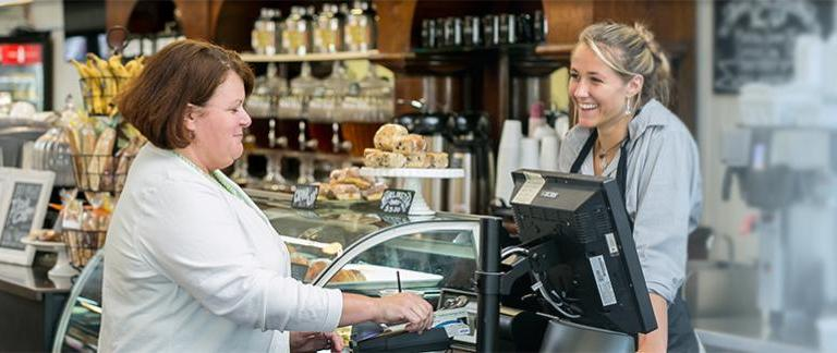A woman talking to a cashier at a coffee shop