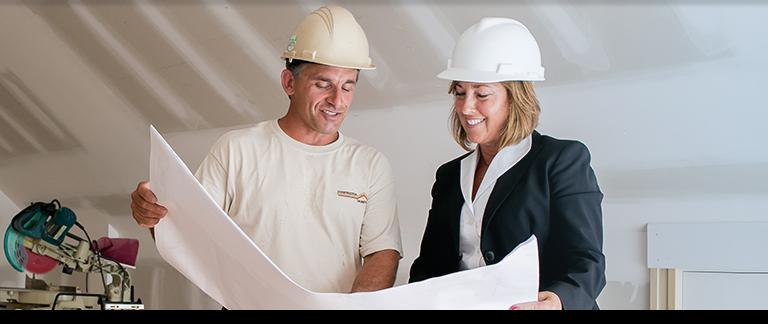 A man and a woman looking at a construction guide