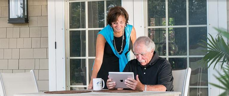 A man looking at an ipad with a woman