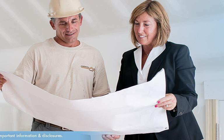 A man and woman looking at a construction guide