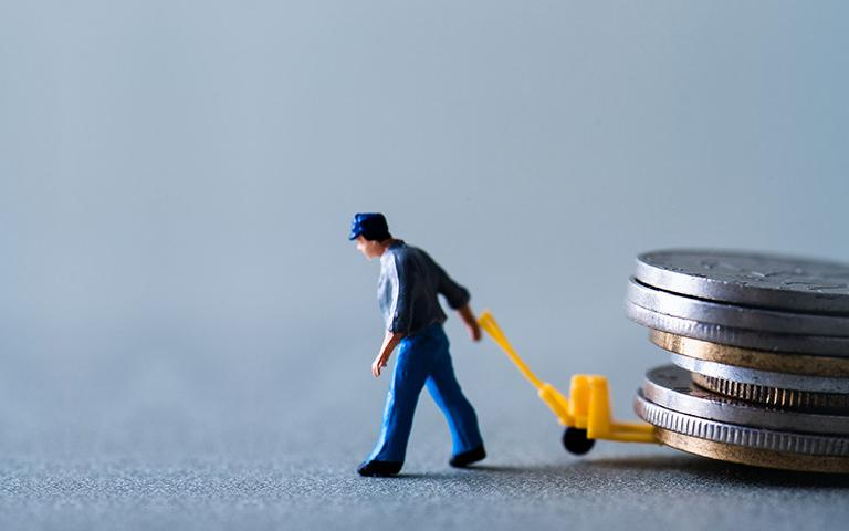 A small plastic figure of a man carrying coins